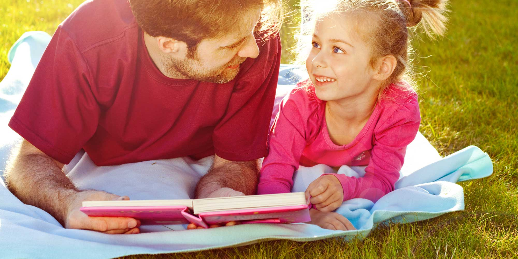 father and daughter laying down on grass reading book