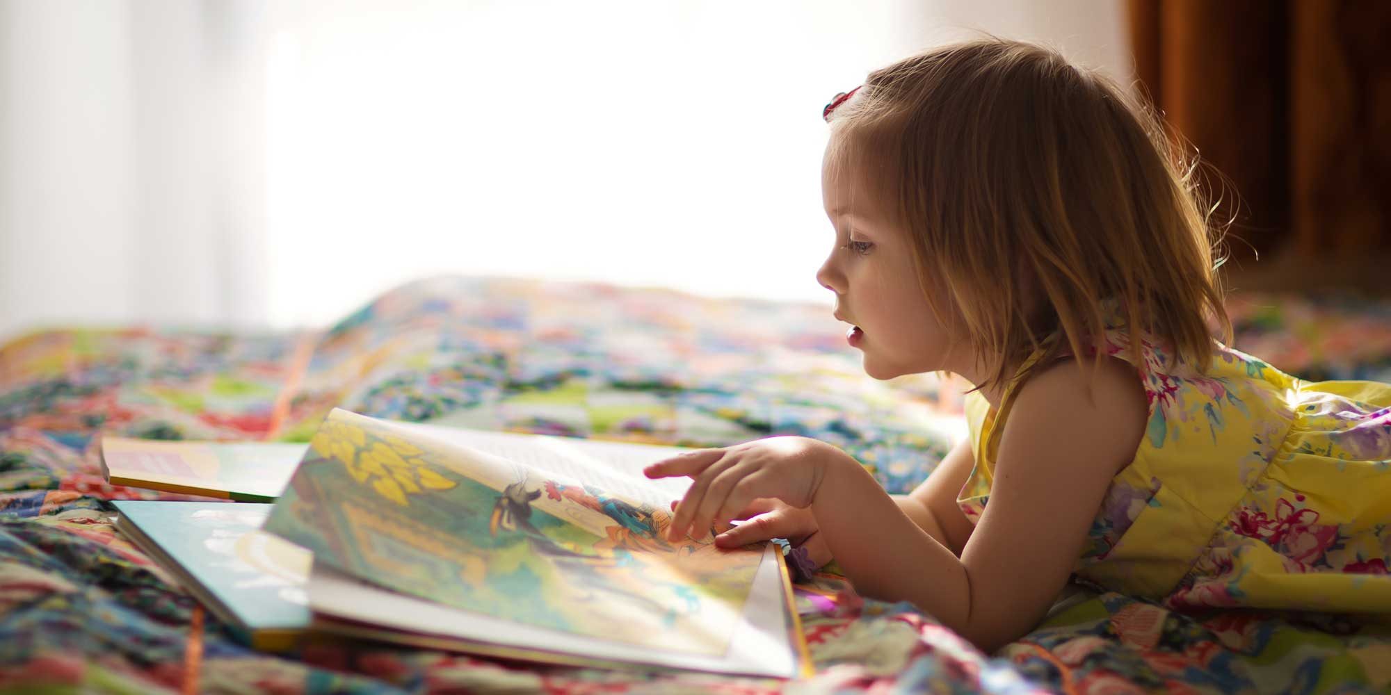 girl reading book mouthing word