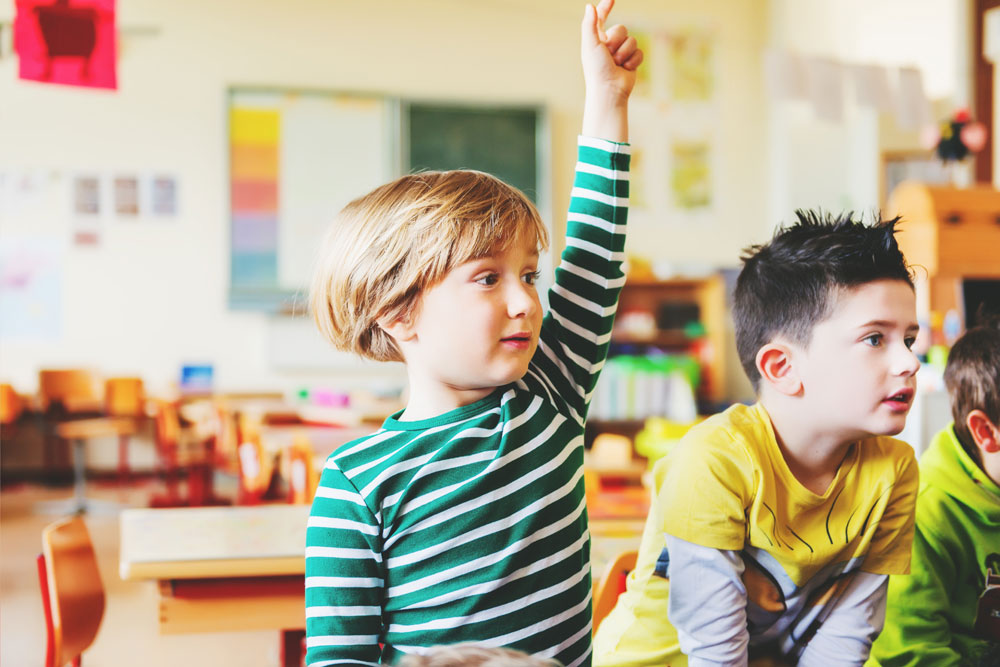 young boy in classroom with hand raised