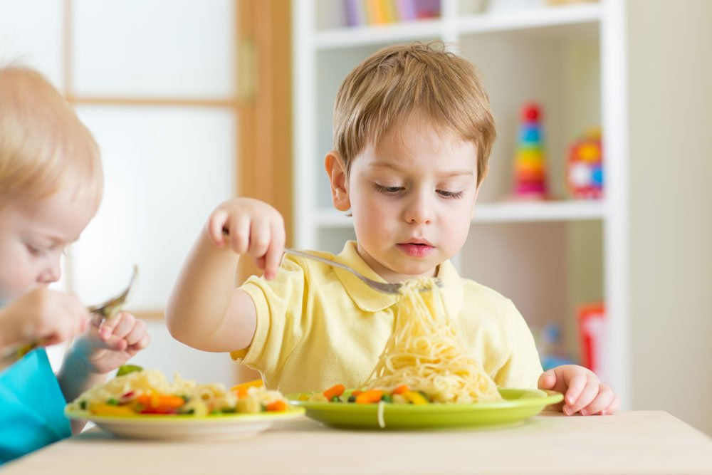 toddler eating pasta with fork