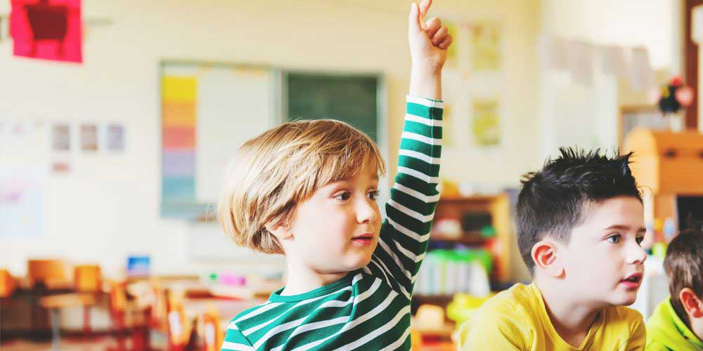young boy in striped top raising hand in classroom
