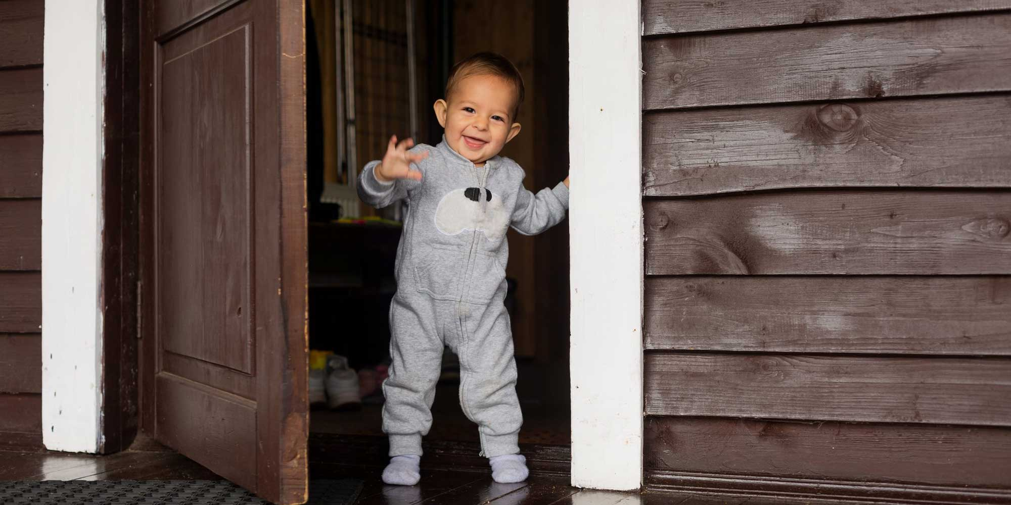 smiling toddler opening front door