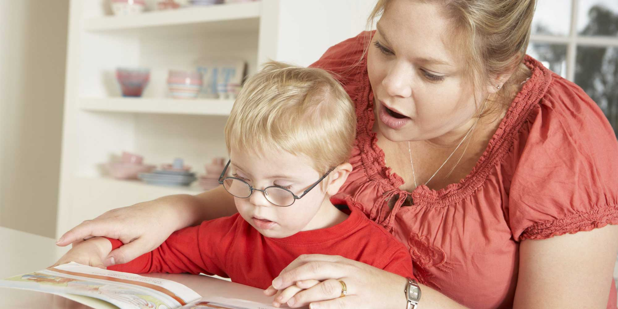 mother teaching child to read from book