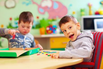 young boy playing with letters on table