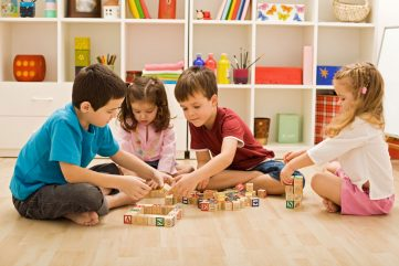 young children playing with wooden blocks with letters on