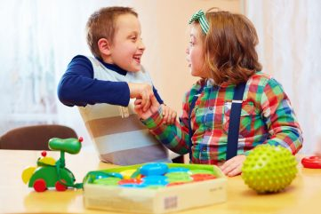 two children pulling hands while playing with toys