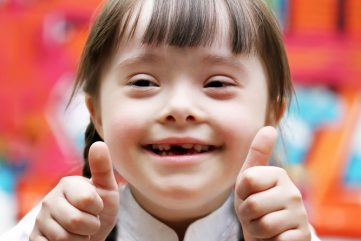 young girl giving double thumbs-up to speech pathology services