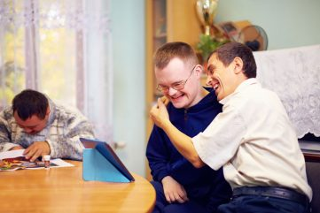 man hugging other man in-front of tablet on table